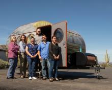 Researchers stand in front of a camper painted with desert scenes